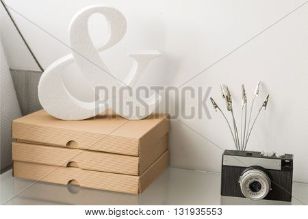 Shelf in a bright room decorated with cardboard boxes analogue photo camera and styrofoam decorative item
