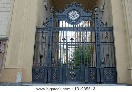 Image contains of a closed gate looking onto a yard