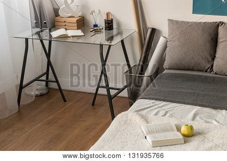 Bedroom corner with glass desk top and metal trestles with personal items on top and a large bed in grey beside
