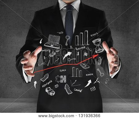 businessman holding business icons on his hand on concrete background
