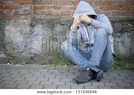 portrait of handcuffed man with face hidden by sweatshirt hood