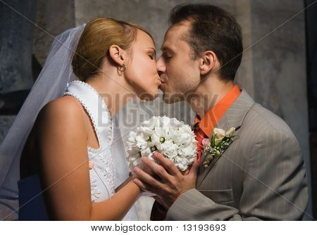 Just married couple kissing holding a round bouquet of white flowers