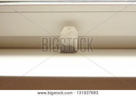 Tea bag on white windowsill close up