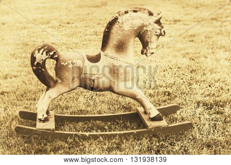 Nice vintage rocking horse at yellow sepia like sign of past time