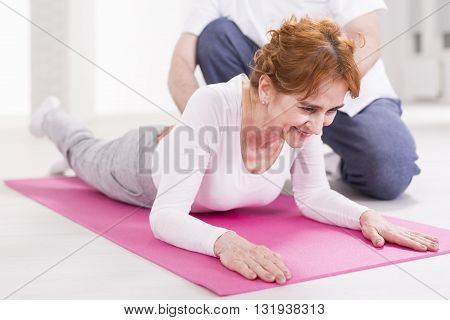 Woman lying on floor during exercises with physiotherapist