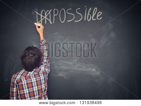 boy putting a cross over impossible on blackboard, retro toned