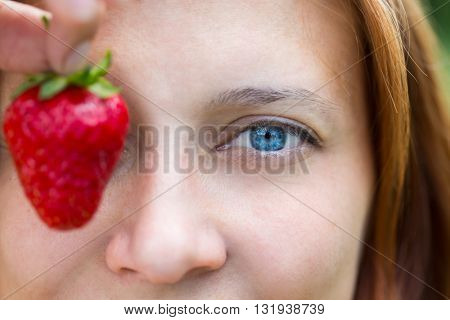woman blue eye with strawberry