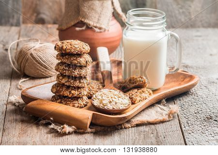 Oatmeal cookies with milk on tray on rustic wooden table