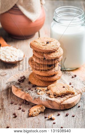 Chocolate chip cookies with milk on burlap and rustic wooden table