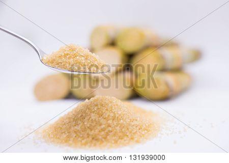 Close Up Brown Sugar In Spoon  On Sugarcane Blur Background