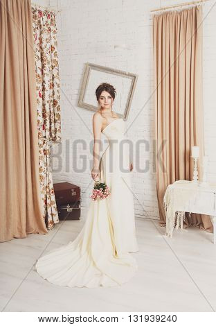 Wedding dress fashion. Beautiful young bride in vintage, shabby chic wedding dress with bridal bouquet. Girl model in champaigne color rustic dress in decorated interior, studio shot, high key