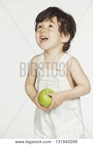 Cute little boy with green apple on white background