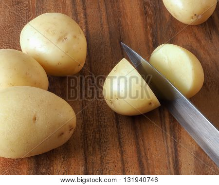 A small pale skinned potato being cut in half with a large kitchen knife on a dark colored wooden cutting board with whole potatoes surrounding.