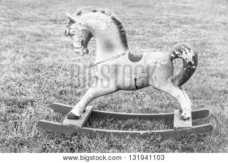 Nice vintage rocking horse on summer grass in black and white colours
