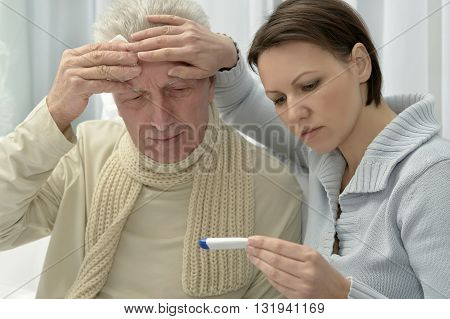 ill Senior man and caring daughter with thermometer