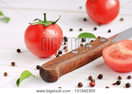 Fresh tomato and wooden knife close-up. Pepper corns scattered white table. Preparing healthy salad snack.