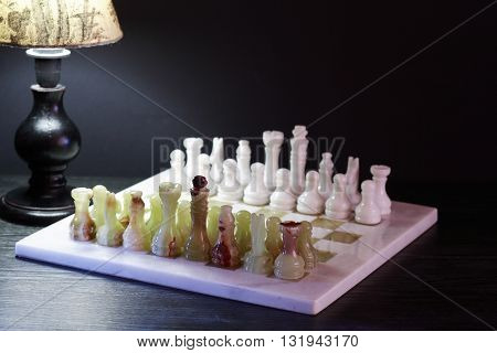 Set of chess pieces made from Onyx on board near desk lamp