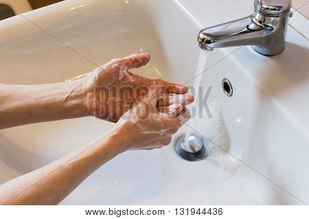 Woman Washing Hands With Soap In The Sink