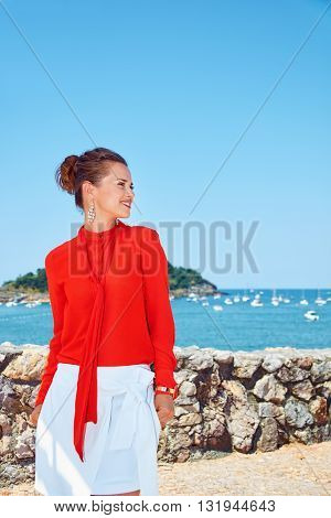 Happy Woman Looking Aside In Front Of Lagoon With Yachts