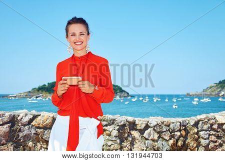 Happy Woman Standing In Front Of Lagoon And Writing Sms