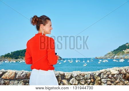 Seen From Behind Woman With Mobile Standing In Front Of Lagoon