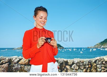 Happy Woman In Front Of Lagoon Checking Photos In Digital Camera
