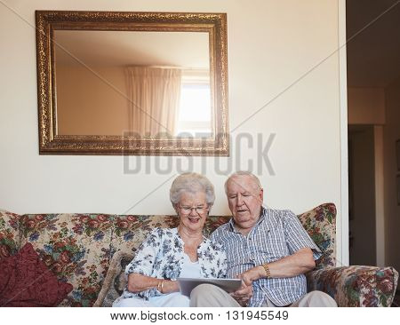Loving Senior Couple Using Digital Tablet At Home