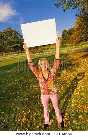Beautiful girl on autumn background holding a white noticeboard