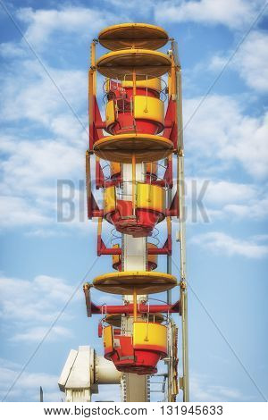 Ferris wheel in amusement park with cloudy blue sky background.