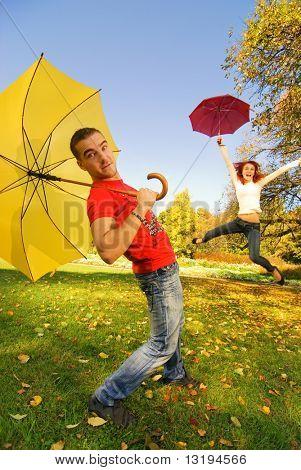 Lustige Paar mit Sonnenschirmen auf Herbst Hintergrund