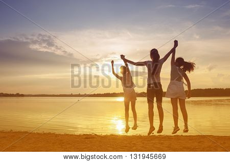 family at sunset on the lake in the summer