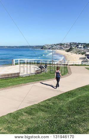 A woman walks along newly constructed coastal walkway at Bar Beach - Newcastle Australia and a beuatiful sunny Autumn day.