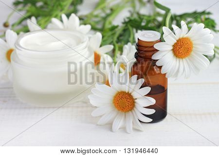 Body cream white essential oil, chamomile daisy flowers. Herbal cosmetic products. Soft focus.