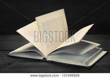 Opened Old Shabby Book With Blurred Text On Wood Background