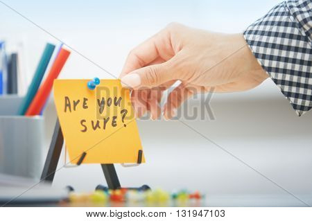 Human hand holding adhesive note with Are you sure text