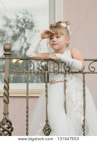 Little Girl In A Ball Gown On The Balcony
