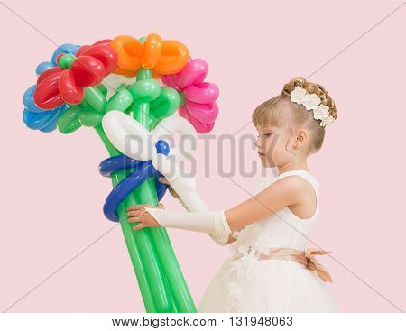 Little Girl With Balloons In A Ball Gown Isolated On A Pink Background