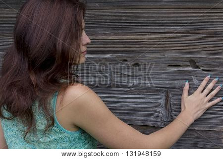 Girl with long hair in a turquoise dress is standing with his back against the background of a wooden wall. He looks at his outstretched hand.