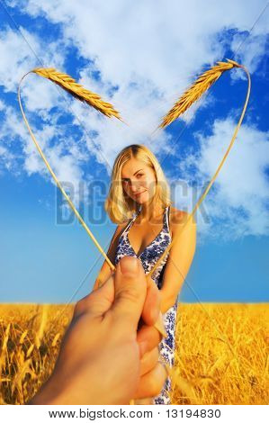 Schönes Mädchen stand im Weizenfeld und Herzen geformte Rahmen um Ihr