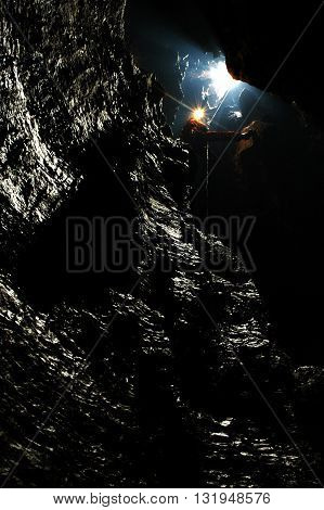 Caver descends in a cave on a rope