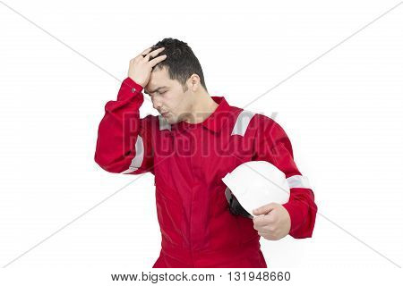 Worker man in depression with hand on forehead. Shocked Male Construction Worker in uniform with hands on his head holding safety helmet - Isolated.