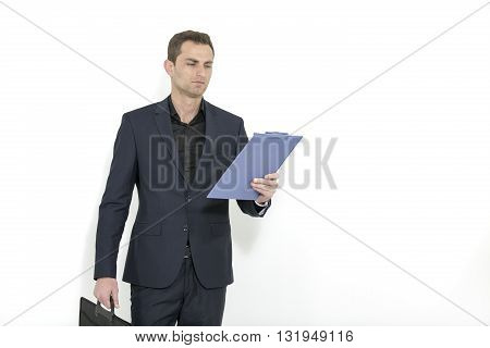 Handsome businessman, construction supervisor, architect.  Studio shoot. Full-length portrait of businessman handing briefcase and reading docs, isolated on white. Concept of business and success