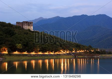 mountain lighted lake at sunset with castle on hill