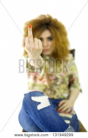 Bad woman is showing fuck off with the middle finger. Woman showing middle finger beautiful girl, red-haired girl. Fuck You