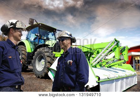mechanics standing in a tractor yard, latest model of tractor and mower