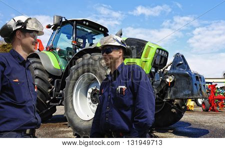two mechanics, farmers with large tractors in background