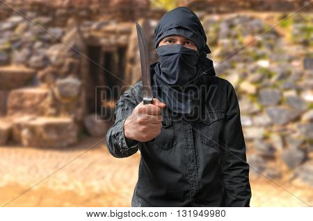 Terrorism concept. Terrorist threatening with knife in desert.