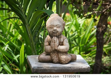 Buddhist statue in tropical garden. Thailand. Close up