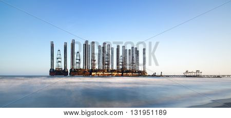 beach waves with oil platform in ocean. Caspian sea offshore oil rig drilling platform off the Baku, Azerbaijan.
