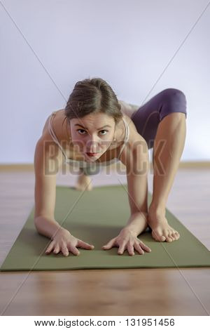 Young woman doing yoga in studio. shot of a young fit woman doing yoga exercises. Full length of a young woman stretching body.